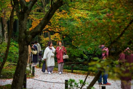 temple tank: KYOTO, JAPAN - NOVEMBER 13, 2015: Unidentified women with Traditional kimono enjoy Autumn Japanese garden in Enkoji temple. Here is located in northern Kyoto and famous during fall colors in Autumn. Editorial