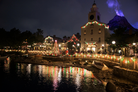 TOKYO, JAPAN- NOVEMBER 08, 2015: Christmas tree and town hall building with light decoraton against Mount Prometheus at Tokyo Disney Sea, opened in 2001 with 176 acres area.