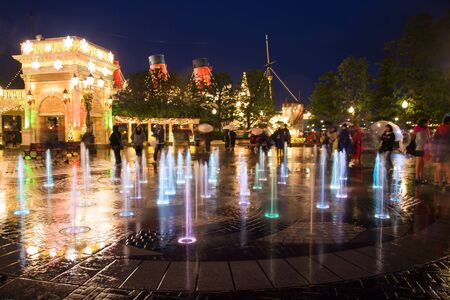 TOKYO, JAPAN- NOVEMBER 08, 2015: Unidentified people at Colorful music fountain at night in Tokyo Disney Sea, opened in 2001 with 176 acres area.