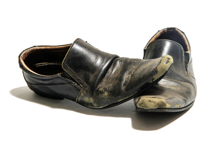 Pair of old dirty shoe isolated on a white background