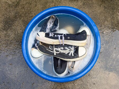 soapy water: Many Shoes or sneakers in a wash basin with soapy water