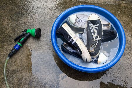 soapy water: water hose or spray and many Shoes in a wash basin with soapy water Stock Photo