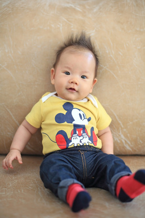 spiky hair: Portrait of Cute smile asian boy with spiky hair on leather sofa