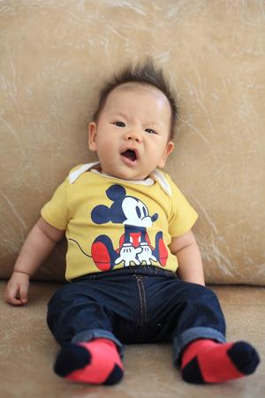 spiky hair: Cute asian boy with spiky hair on leather sofa Stock Photo