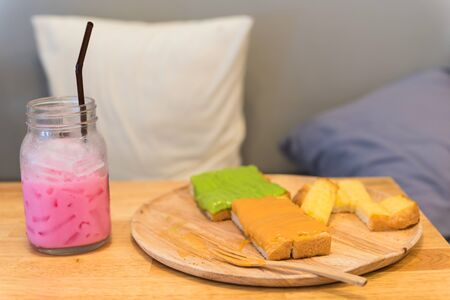 unhealthy lifestyle: Sweet Bread toast and cold ice pink milk on table, Leisure eating with unhealthy lifestyle
