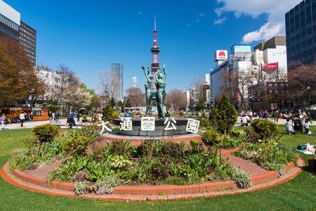 odori: SAPPORO, HOKKAIDO, JAPAN - APRIL 24, 2016: dance woman statues stand in front of sapporo TV tower in Odori Park.