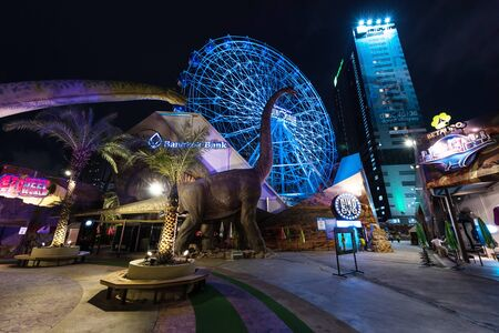 BANGKOK, THAILAND - JUNE 17, 2016: Fake dinosaurs and Ferris wheel at night in Dinosaur planet, theme park in downtown opened since March 25, 2016. Selective focus at Ferris wheel. Redakční