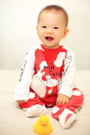 clothes interesting: Laugh cute asian baby with red cow pajama on the bed. Studio shot with 6 months old boy Stock Photo