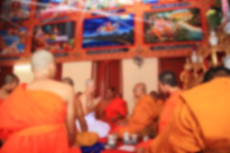 ordain: Blurred abstract image of Newly ordained Buddhist monk inside temple. Stock Photo