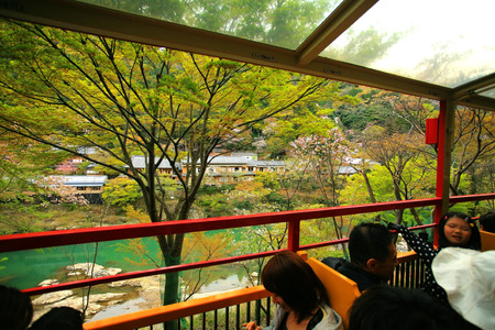 KYOTO, JAPAN - APRIL 17, 2011 : Unidentified tourists sightseeing natural view from Sakano Romantic Train, a sightseeing retro train that runs along mountain pass through sakura tunnel .