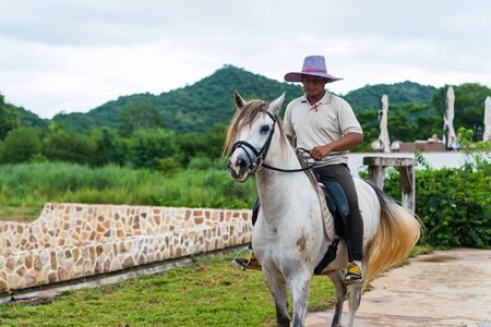 korat: KORAT, THAILAND - JULY 30, 2016: Unidentified man riding white horse at the farm at Kao Yai in Nakhon Ratchasima. riding horse is famous activity here. Editorial
