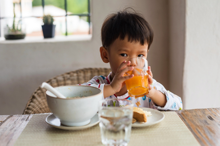 in pajama: Asian cute boy with pajama drink orange juice and eat breakfast, bread and rice soup
