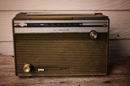 transitor: Old radio or transistor on wooden table, vintage color process
