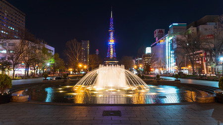 odori: SAPPORO, HOKKAIDO, JAPAN - APRIL 24, 2016: night cityscape of beautiful fountain in Odori park and Sapporo TV tower .
