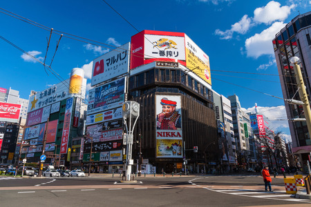 SAPPORO, HOKKAIDO, JAPAN - APRIL 24, 2016: Susukino junction with landmark of Nikka banner advertisment against blue sky, Here is  is a red-light district in Sapporo, Hokkaido.