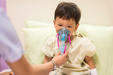 to inhale: Sick boy inhale medication by inhalation mask to cure Respiratory Syncytial Virus (RSV) Stock Photo