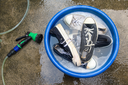 scour: Shoes or sneakers in wash bucket with soapy water and water hose