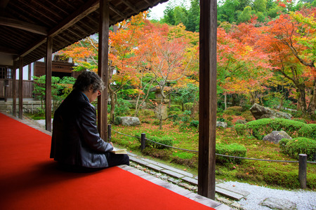 temple tank: Old Japanese woman draw picture of Enkoji temple with fall color in Kyoto, Japan.