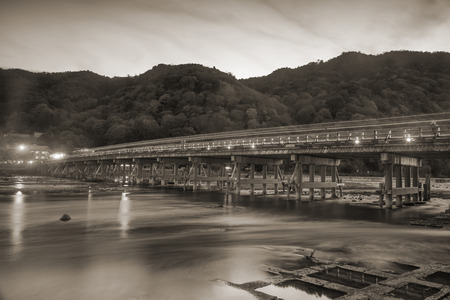 light trail: Arashiyama bridge with light trail at night, Kyoto, Japan. Black and white or sepia color process Stock Photo