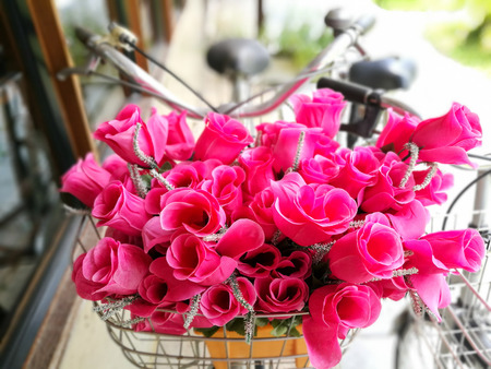 Fake pink flowers in basket of bicycle Stock Photo