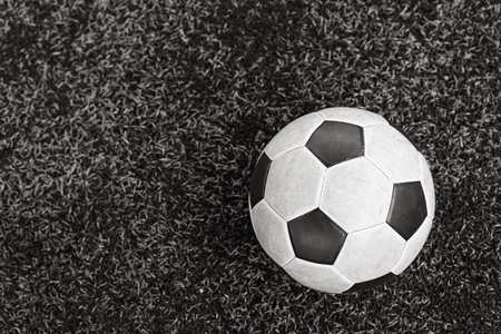 onset: Football on field of artificial green grass, black and white process