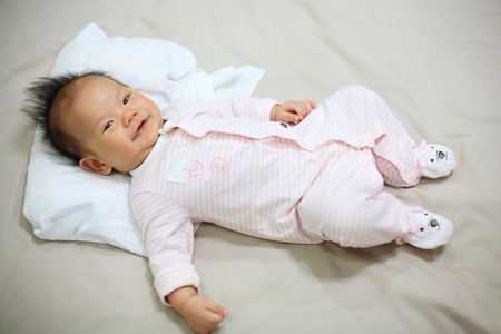 Adorable 3 months old baby boy smile on the bed Stock Photo