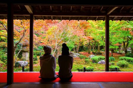 temple tank: Japanese girls sit in Enkoji temple to see fall Japanese foliage, Momiji, garden in Kyoto, Japan. Here is Rinzai Zen Sect and very famous during Autumn.