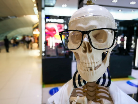 Fake human skull with black glasses. Selective focus at glasses. Banco de Imagens
