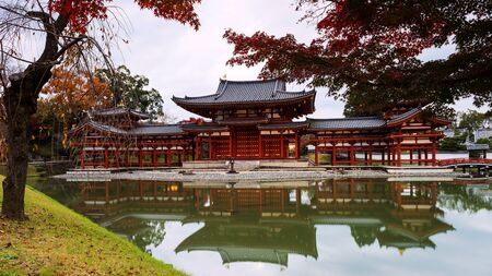 Byodo-ins Phoenix hall with autumn colors in Uji, Kyoto, Japan. Here is the most famous Uji landmark jointly with temples of the Jodo-shu and Tendai-shu sects. Editorial