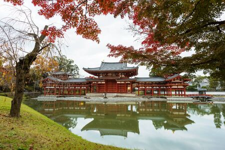 Byodo-ins Phoenix hall with autumn foliage and reflection in Uji, Kyoto, Japan. Here is the most famous Uji landmark jointly with temples of the Jodo-shu and Tendai-shu sects. Stock Photo
