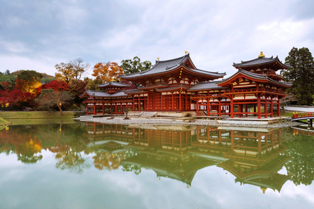 Byodo-ins Phoenix hall with fall colors at dusk in Uji, Kyoto, Japan. Here is the most famous Uji landmark jointly with temples of the Jodo-shu and Tendai-shu sects.