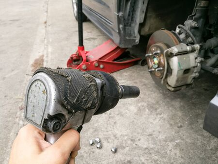 screwing: screwing mechanic tool on hand to remove car tire at the garage Stock Photo