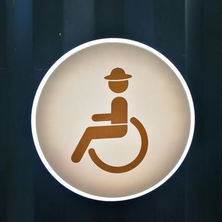 sex traffic: handicap toilet sign on blue zinc metal wall