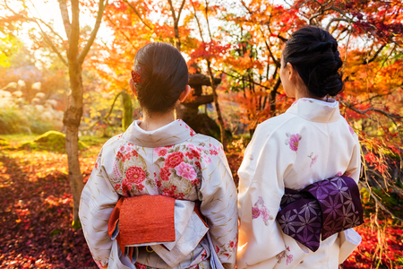 Kimono girls enjoy autumn red maple colors against sunset at Eikando temple, Kyoto, Japan