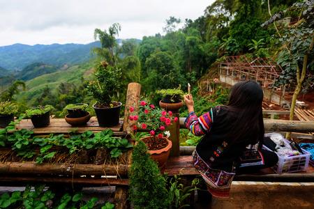Cute girl with Traditional Akha dress, selfie at top of Mae Salong hill, Chiang Rai, Thailand
