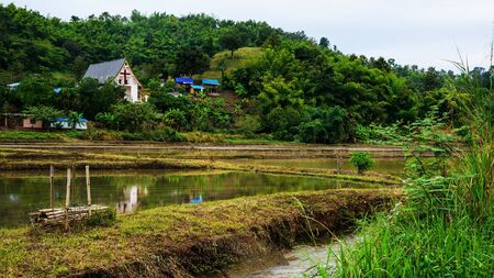 loess: Christian church at green countryside meadow with reflection in Chiang rai, Thailand Stock Photo