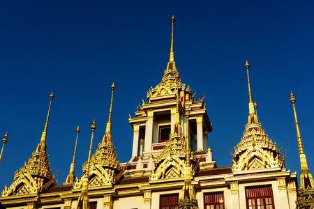 Loha Prasat at Wat Ratchanadda, new golden roof against blue sky, Bangkok, Thailand