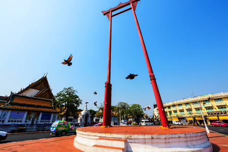 BANGKOK, THAILAND:  FEBUARY 13, 2017: Birds flying through Red Giant Swing near wat Suthat, Bangkok, Thailand. Here is one of the most famous Bangkok landmarks. Editorial