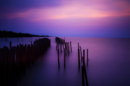Twilight sky over soft motion sea and silhouette bamboo logs. Super long exposure by big stopper.