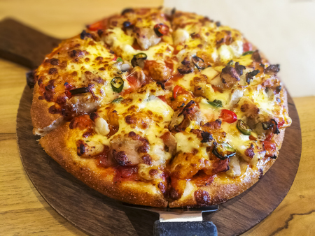 cut delicious fresh pizza in a pan on wooden table