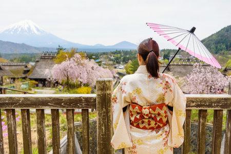 saiko: Japanese Kimono girl with umbrella by rear view at Saiko Iyashi no Sato Nenba, former farming, village with Cherry blossom or sakura and Mt. Fuji, Yamanashi, Japan