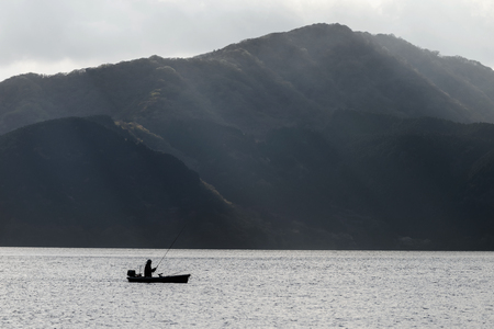 Fishing on Ashi lake with sun rays against the mountain, Hakone, Japan. Black and white process