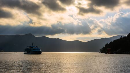HAKONE, JAPAN - MAY 4, 2017: sight seeing ship on Ashi lake with Red torii gate of Hakone shrine against sun rays before sunset. Editorial