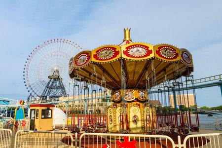 YOKOHAMA, JAPAN - MAY 6, 2017: Merry-go-round and Ferris wheel at amusement park  in Minato Mirai waterfront district. Here is the most famous landmark in Yokohama.