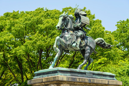 TOKYO, JAPAN - MAY 8, 2017: Statue of the great samurai Kusunoki Masashige isolated on white background. It located at the East Garden outside Tokyo Imperial Palace, Japan