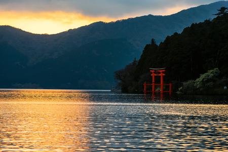 Lake Ashi and red Torii gate during sunset in Hakone, Japan
