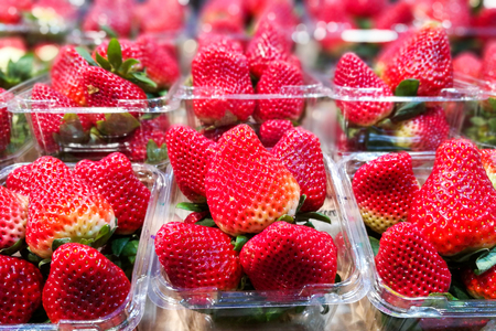 Big strawberries in plastic containers for sale