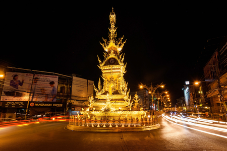 CHIANGRAI, THAILAND - JANUARY 8, 2017 : Golden Clock Tower Designed by Chalermchai Khosit Pipat, with street light trail.