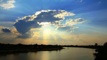 Beautiful cloud formations over river at sunset with sun beams through clouds