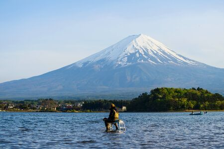 Rear shot of Japanese man sitting on iron ladder above clear water of Kawaguchiko lake to fishing with Mount Fuji view behind, , Fujikawaguchiko, Japan. Here, 1 of 5 Fuji lakes, is the most famous.